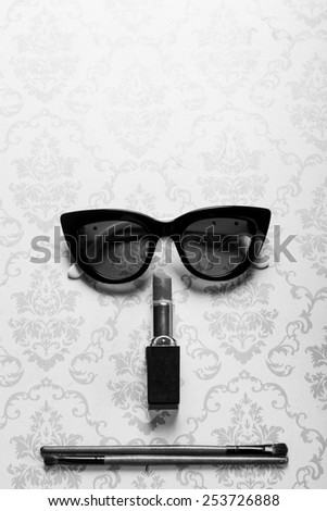 A straight face made of sunglasses, lipstick, and shadowing eyebrushes. - stock photo