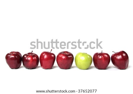 A straight line of red apples with one green apple. - stock photo