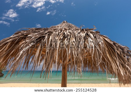 A straw umbrella on a beautiful tropical beach - stock photo