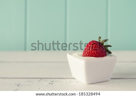 A strawberry on a bowl with greek yogurt over a white wooden table with a robin egg blue background. Vintage look. - stock photo