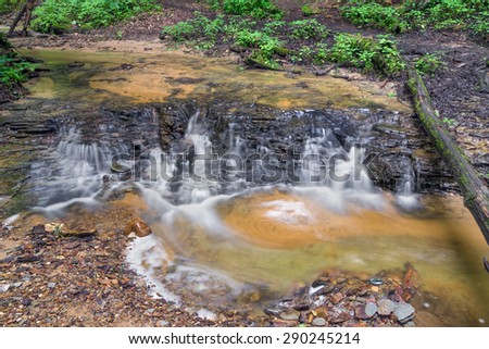A stream cascades over a small rock ledge in Shades Start Park, Indiana. - stock photo