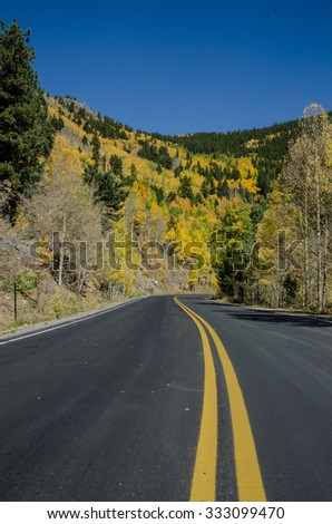 A street level view of a winding road in Colorado in the fall - stock photo