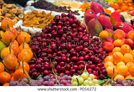 A street market with a range of fruits for sale. Focus on the cherries.