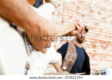 A street musician playing his guitar close up - stock photo