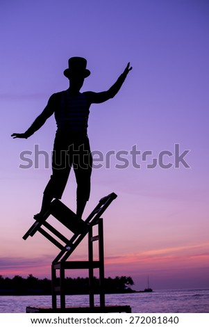 A street performer balancing on chairs during the Sunset Celebration Mallory Square, Key West, Florida - stock photo