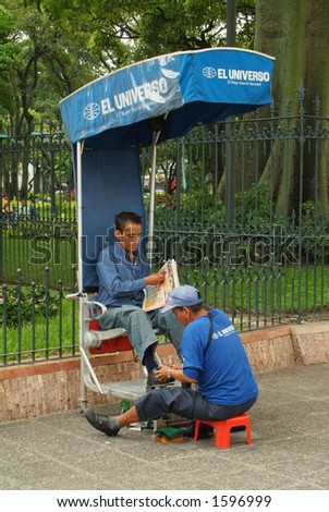 A street shoe-siner cleans a man's shoe while he reads a newspaper (Ecuador, South America)