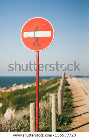 "A street traffic sign, ""victim"" of street art, in a very known surf zone in Portugal (Baleal, Peniche). Surf Zone. - stock photo"