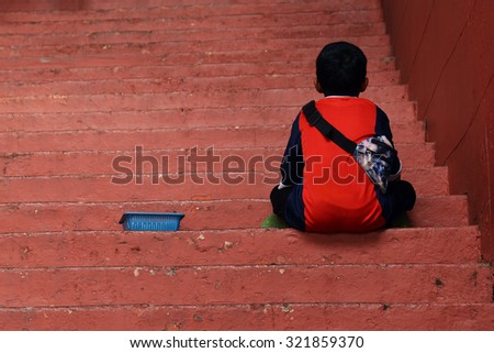 A street young Seller is sitting and waiting on the red step at a Christ Church in Melaka Malaysia - stock photo