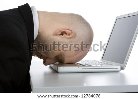 A stressed bald businessman with his forehead resting on the laptop computer keyboard. - stock photo