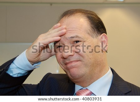 A stressed businessman, with hand to head