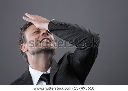 A stressed out mature businessman holds his head - stock photo
