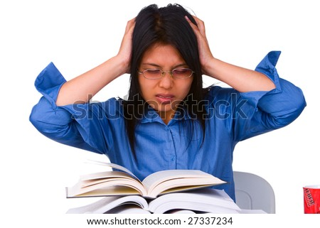 A stressful female student facing a lot of books that she must read. - stock photo