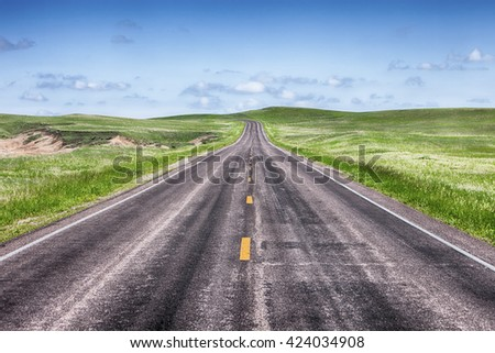 A stretch of straight road in the prairie grasslands of Badlands National Park in South Dakota turns at the horizon to go over the hills.