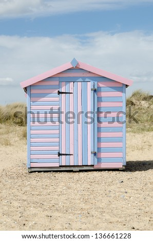 A striped beach hut on a UK shore. - stock photo