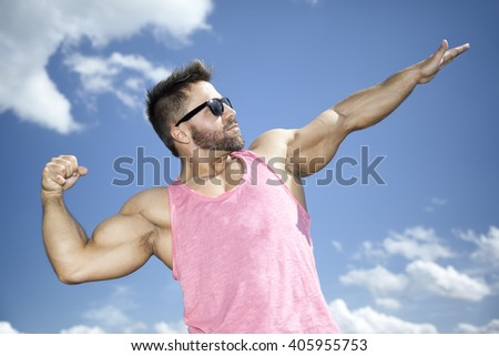 A strong fit man posing in front of the blue sky