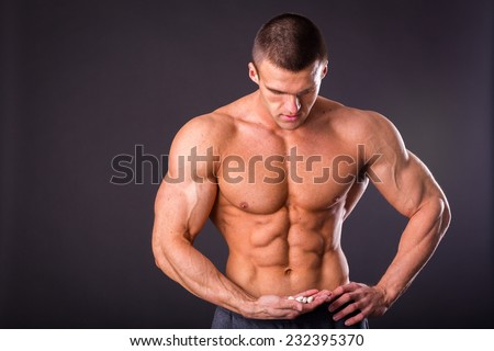 A strong man, bodybuilder, posing on a gray background. A man holding a pill, amino acids, dietary supplements. He looks at them. Sports, bodybuilding, special sports nutrition.