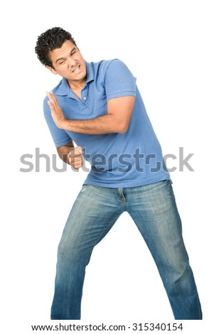 A struggling latino man in blue jeans and shirt defending, forcing, pushing, leaning his shoulder and full body weight against an imaginary inserted heavy object into copy space coming from the side