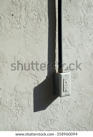 A stuccoed wall with electrical outlet mounted outdoors. - stock photo