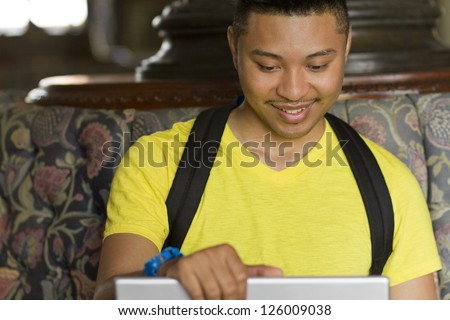A student looks down at a laptop screen - stock photo