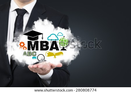 A student's hand is holding a cloud with the educational icons. A concept of the master's degree in business administration, MBA. - stock photo