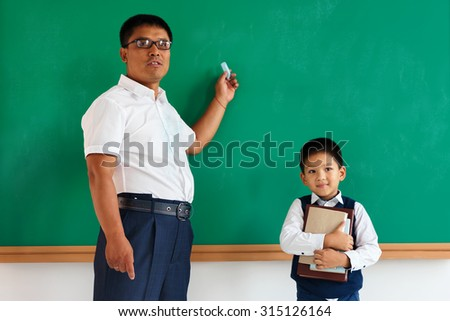 A student with teacher near blackboard in the classroom / photo of teen and teacher school Chinese boy, creative concept with Back to school theme - stock photo