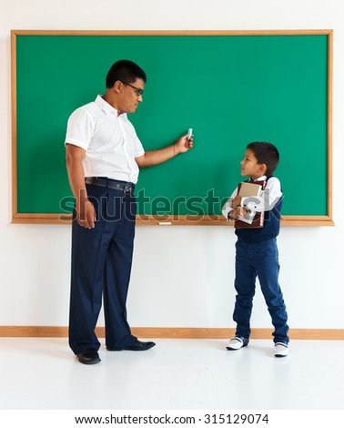 A student with teacher near blackboard in the classroom / photo of teen and teacher school Chinese boy, creative concept with Back to school theme