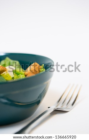 a studio lit shot of a traditional salad with croutons and cheese chunks in a green bowl and fork. with copy space