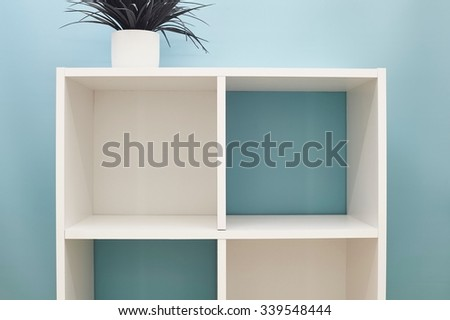 A studio photo of a simple white bookcase - stock photo
