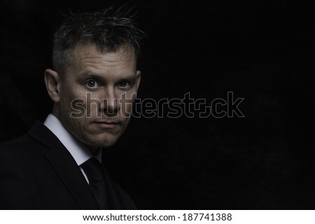 A studio portrait of a confident man wearing a dark suit with a dark background. - stock photo