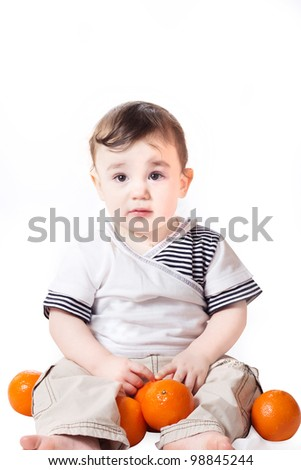 a studio portrait of a nice little boy with oranges