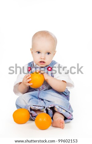 a studio portrait of a nice little child holding an orange in his hand