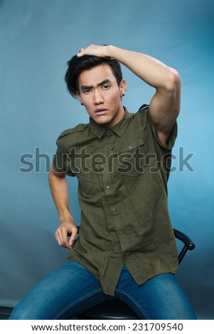 a studio portrait of a young asian male model in stylish casual clothes
