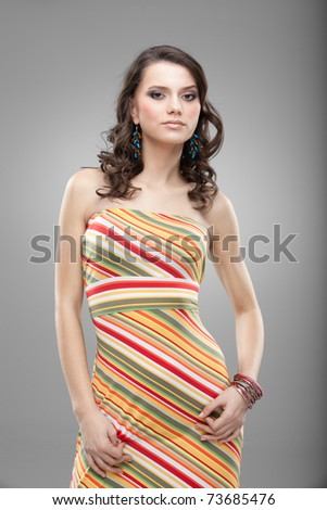 a studio portrait of a young, pretty woman, in colorful clothes and accessories, smiling, with her hands on her hips - stock photo