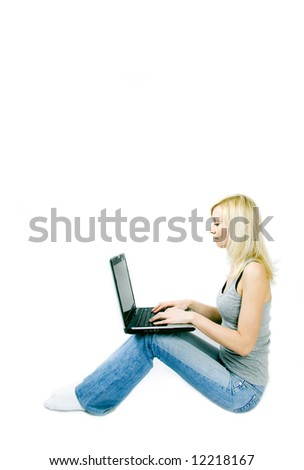 A studio shoot of a beautiful young girl sitting with a computer in her lap.