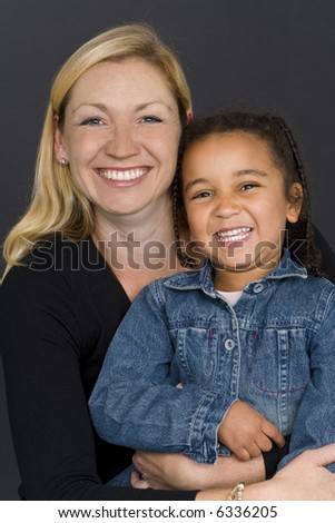 A studio shot of a happy smiling beautiful young mixed race little girl and a caucasian woman in her thirties