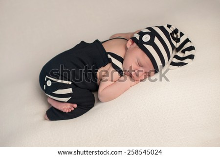A studio shot of a newborn baby boy sleeping on his stomach, wearing a navy blue and white romper with matching hat. - stock photo