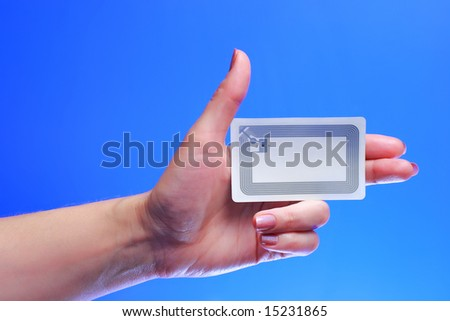 A studio shot of a woman holding in her hand Radio-frequency identification (RFID) tag card. Room for text, or your own message.