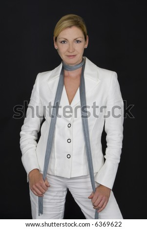 A studio shot of an attractive caucasian woman in her thirties wearing a white suit in front of a black background