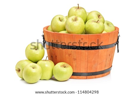A studio shot of green apples in a wooden basket isolated on white background - stock photo