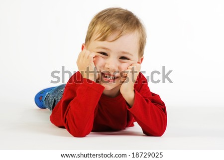 A studio view of a cute little boy lying on the floor.