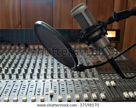 a studio vocal microphone over a mixing board console - stock photo