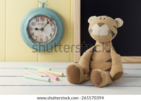 A stuffed animal and some chalks on a white wooden table. In the background a turquoise clock and a blackboard on a yellow wainscot. Vintage - stock photo