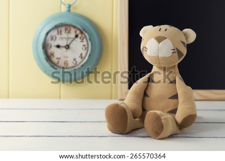 A stuffed animal on a white wooden table. In the background a turquoise clock and a blackboard on a yellow wainscot. Vintage - stock photo
