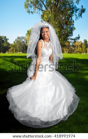 A stunning African American bride holds her dress and begins to twirl for a portrait on her wedding day. - stock photo