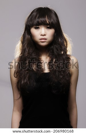 A stunning Chinese girl Poses in the studio. - stock photo