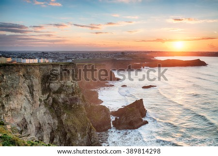 A stunning hazy sunset over cliffs at Porth on the outskirts of Newquay on the Cornwall coast - stock photo