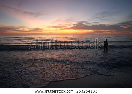 A stunning sunset over the ocean with person gazing