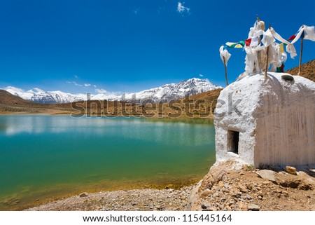 A stupa stands at the edge of a pristine mountain lake used by Buddhist pilgrims near Dhankar, Spiti Valley, Himachal Pradesh, India - stock photo