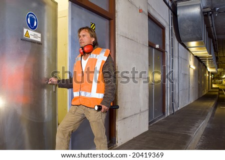 A sturdy looking engineer, opening a door to an engine room in a dimly lit tram tunnel, ignoring the safety precaution to wear his ear protection - stock photo