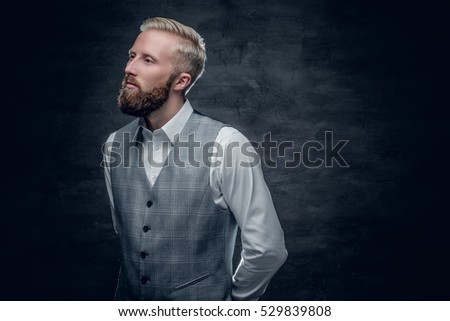 A stylish bearded blond male dressed in a waistcoat.